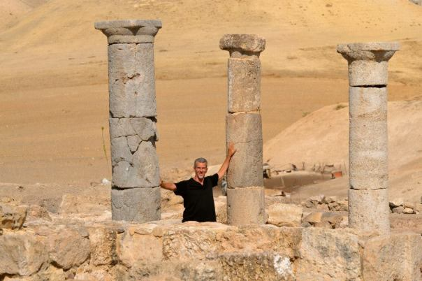 Ron standing between the ancient Roman columns near the churches of Pella